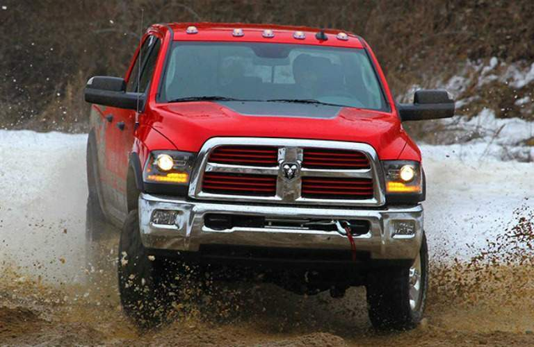 red 2016 Ram 2500 driving off road through mud and water