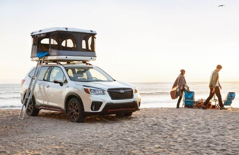 2019 Subaru Forester parked on the beach next to couple