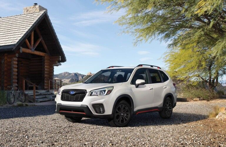 White 2019 Subaru Forester parked next to cabin house