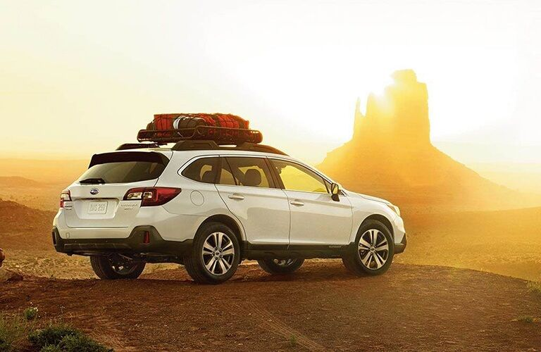 White 2019 Subaru Outback parked cliff side at sunset
