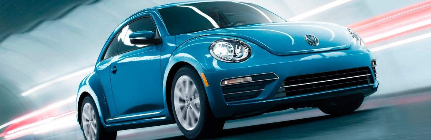 blue 2017 Volkswagen Beetle driving through tunnel