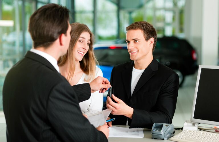 Young couple getting keys to a new car