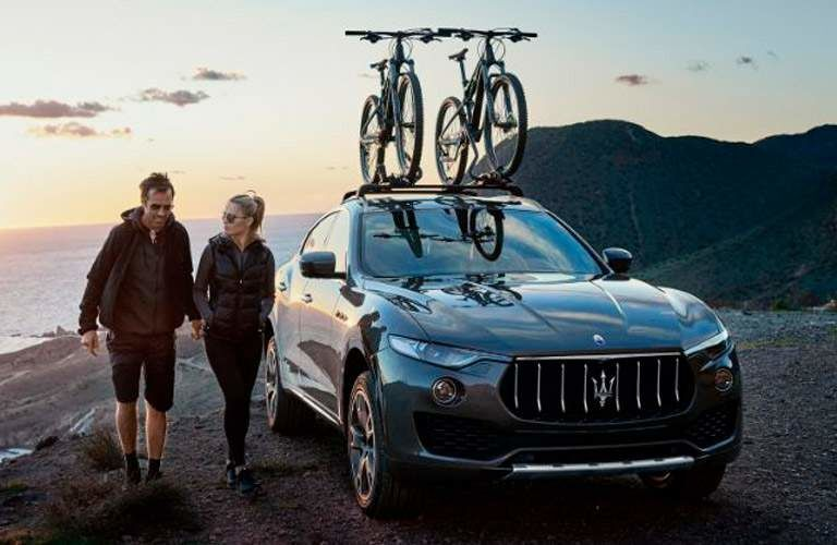 2019 Maserati Levante next to a body of water with two people