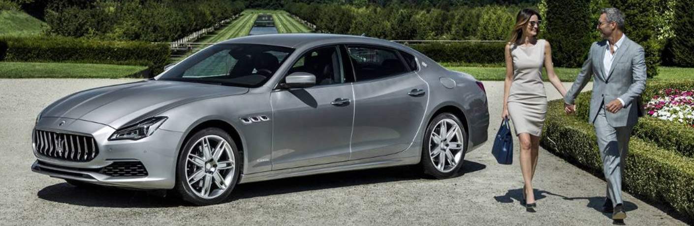 couple walking away from the 2018 Maserati Quattroporte at a country club