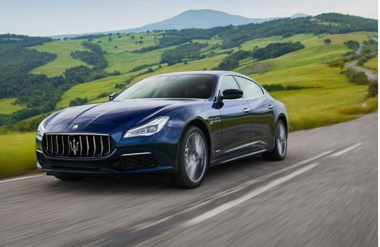 2020 Maserati Quattroporte exterior front fascia driver side on blurred highway with blurred hills behind it