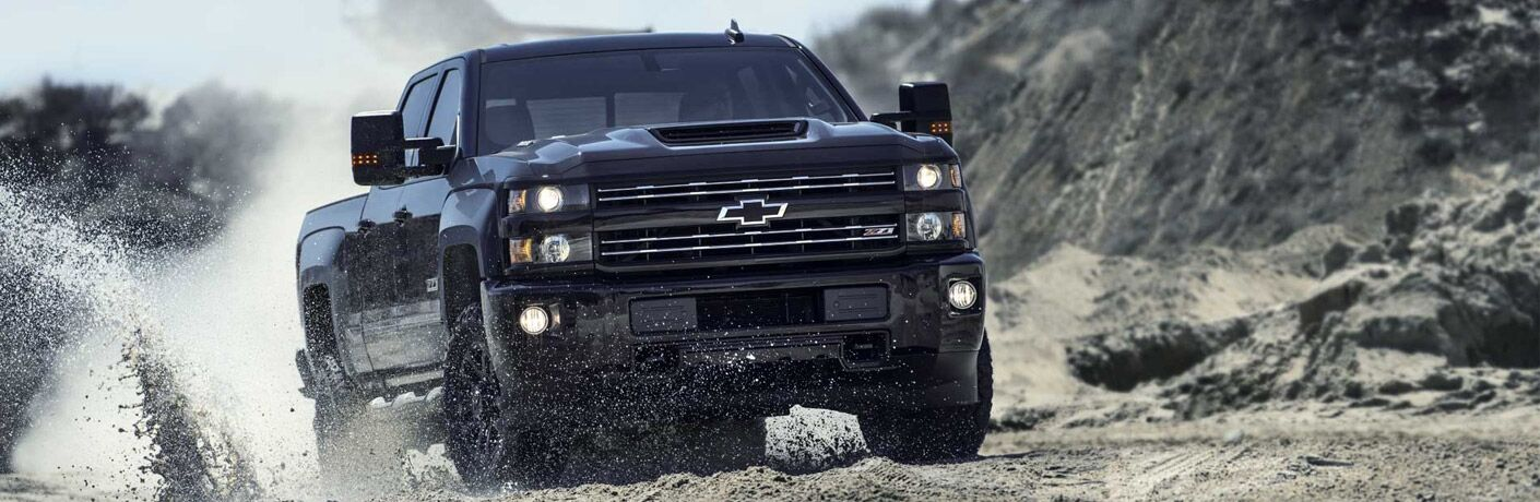 Black Chevy Silverado on a muddy trail