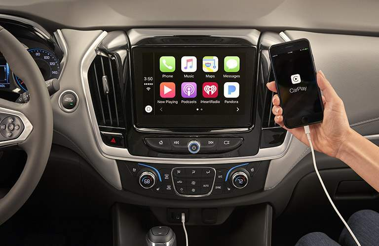 person using 2018 chevy traverse's apple carplay functionality to integrate smartphone