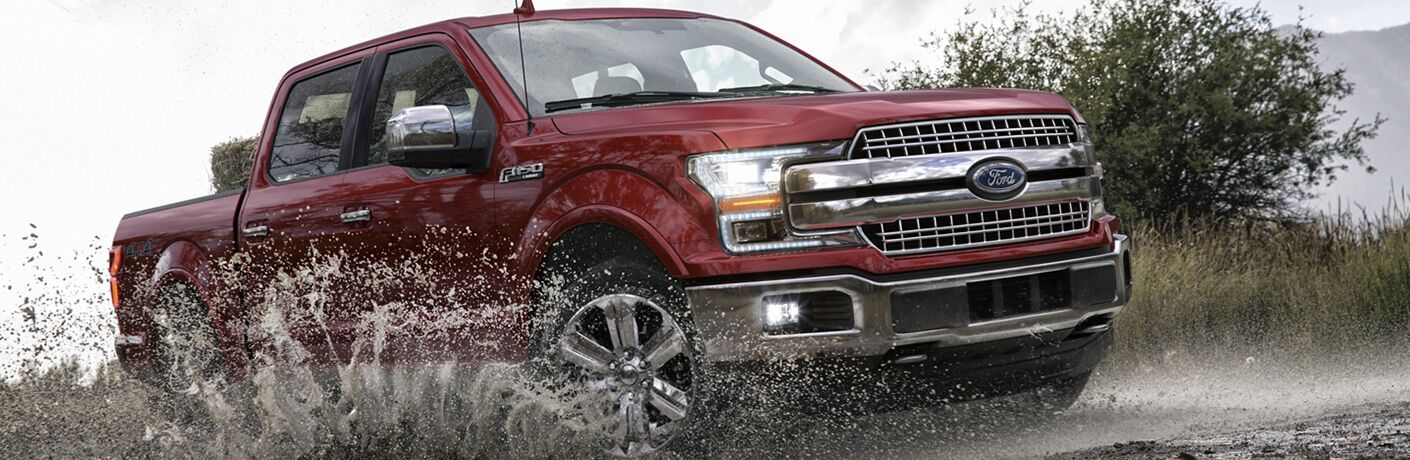Red 2020 Ford F-150 driving through a puddle