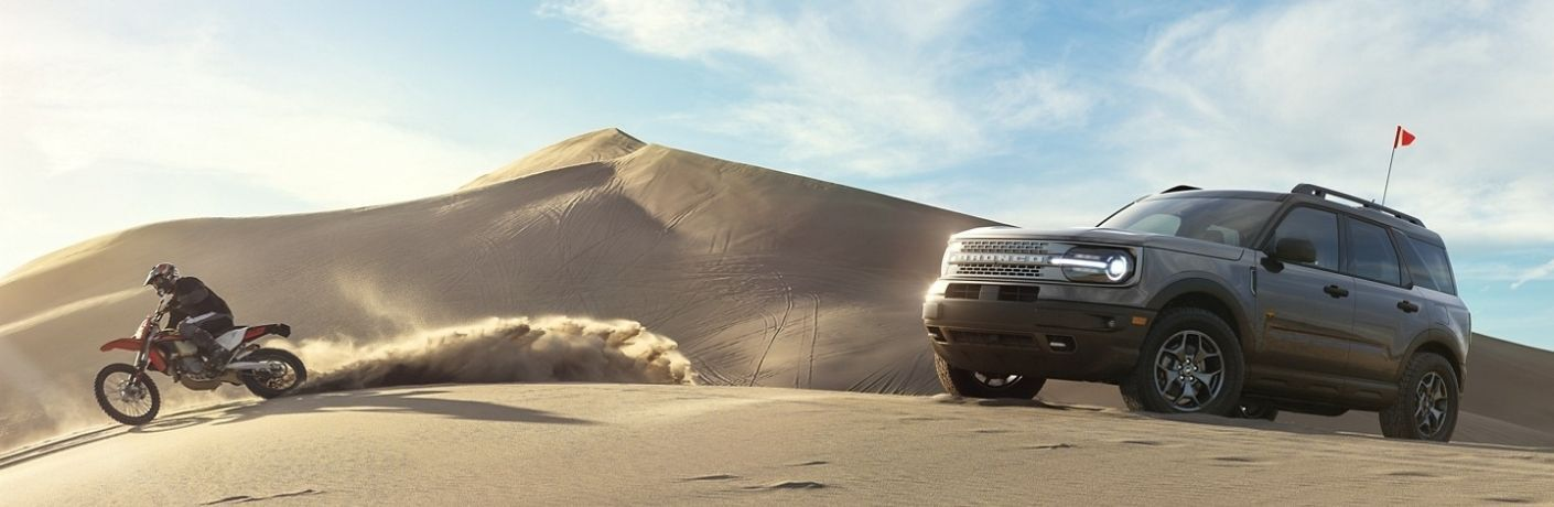 Exterior view of a gray 2021 Ford Bronco Sport parked on a sand dune