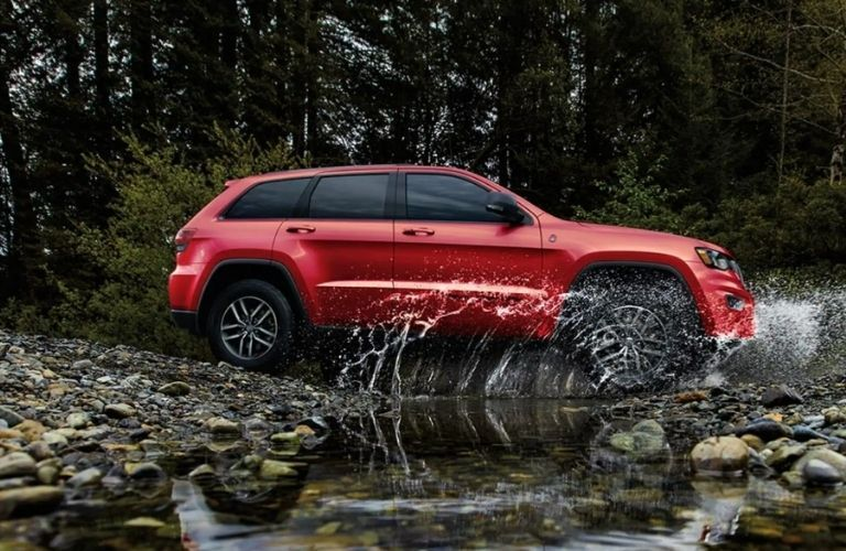 side view of the 2021 Jeep Grand Cherokee splashing water