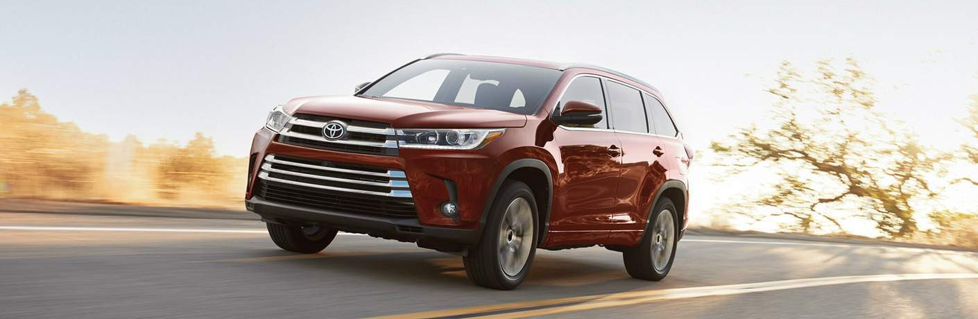 Maroon 2018 Toyota Highlander Hybrid Driving by a Forested Area