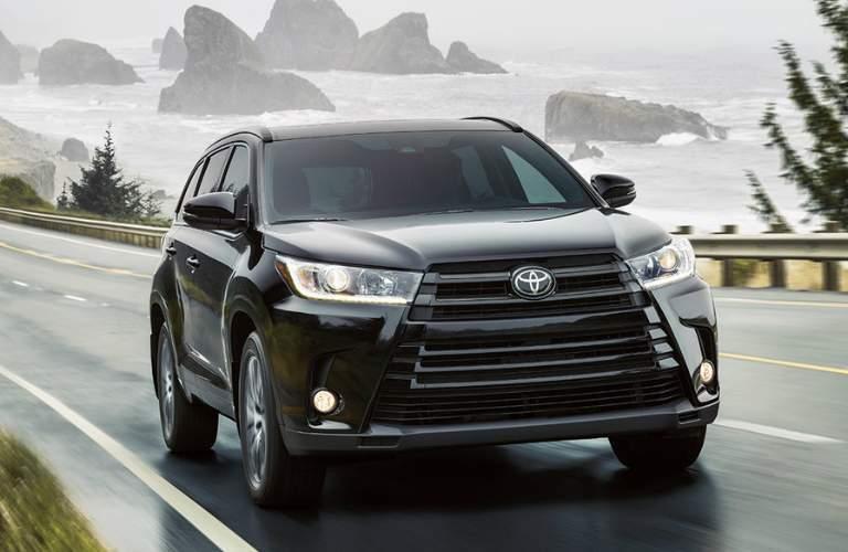 Black 2018 Toyota Highlander Hybrid Driving on a Coastal Highway