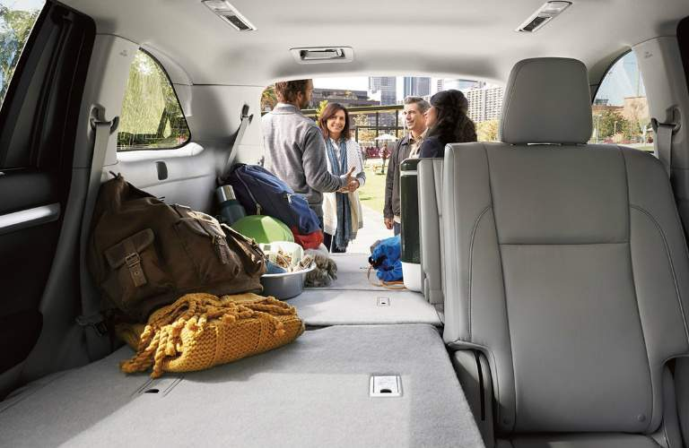 People Having a Conversation Behind the Cargo Area of a 2018 Toyota Highlander Hybrid