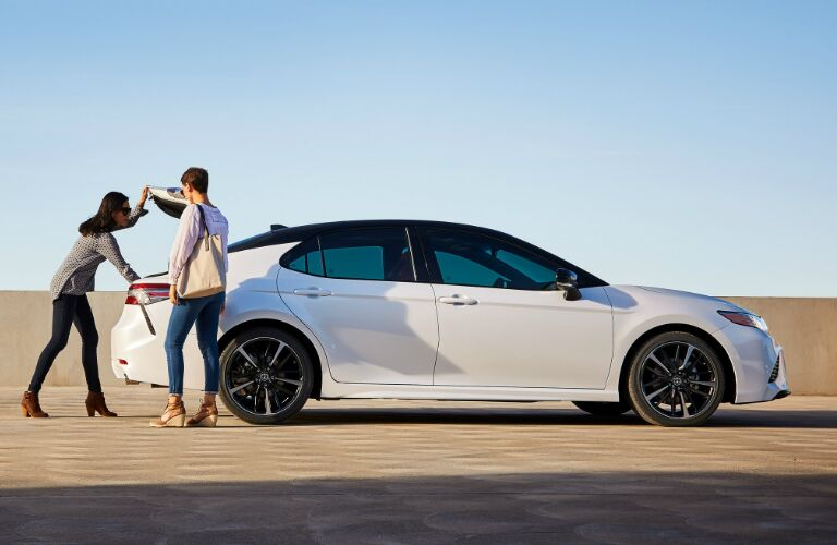Two People Standing Next to the Trunk of a White 2019 Toyota Camry