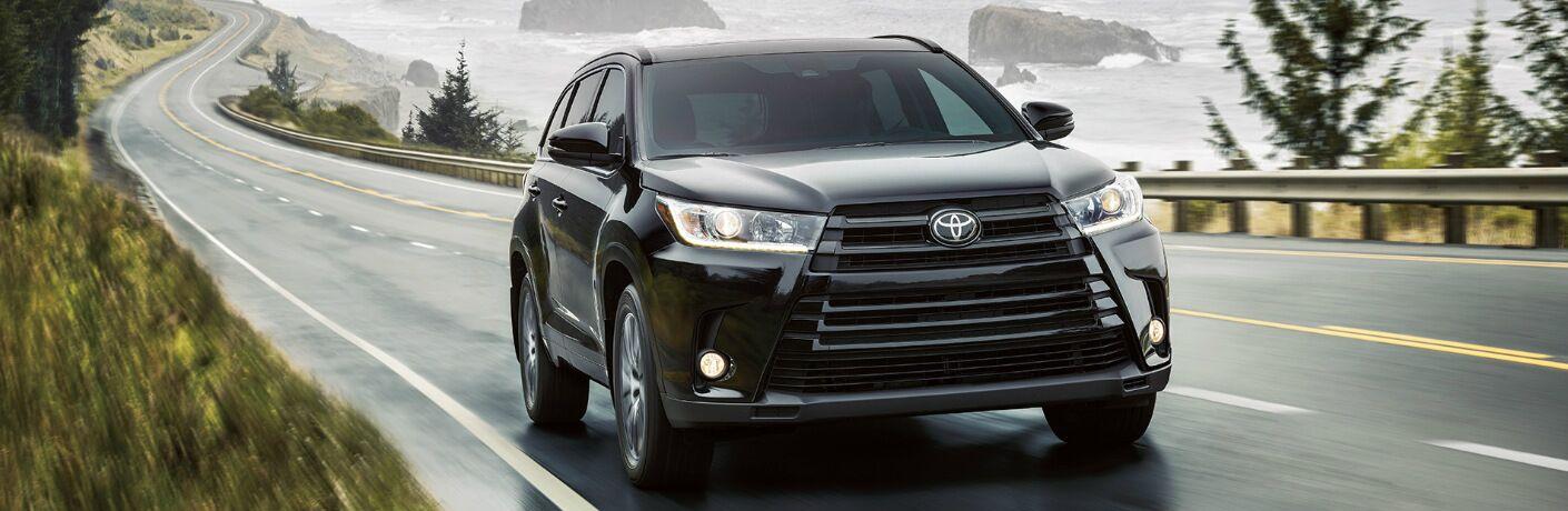 Black 2019 Toyota Highlander Driving on a Coastal Road