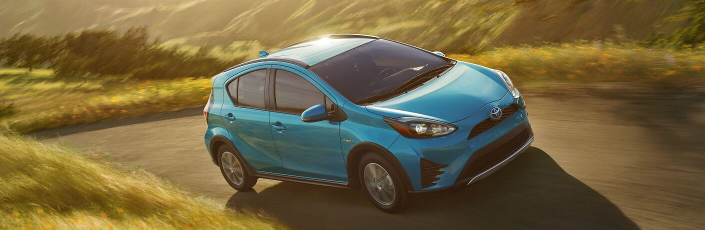 Blue 2019 Toyota Prius c Driving on a Hilly Road
