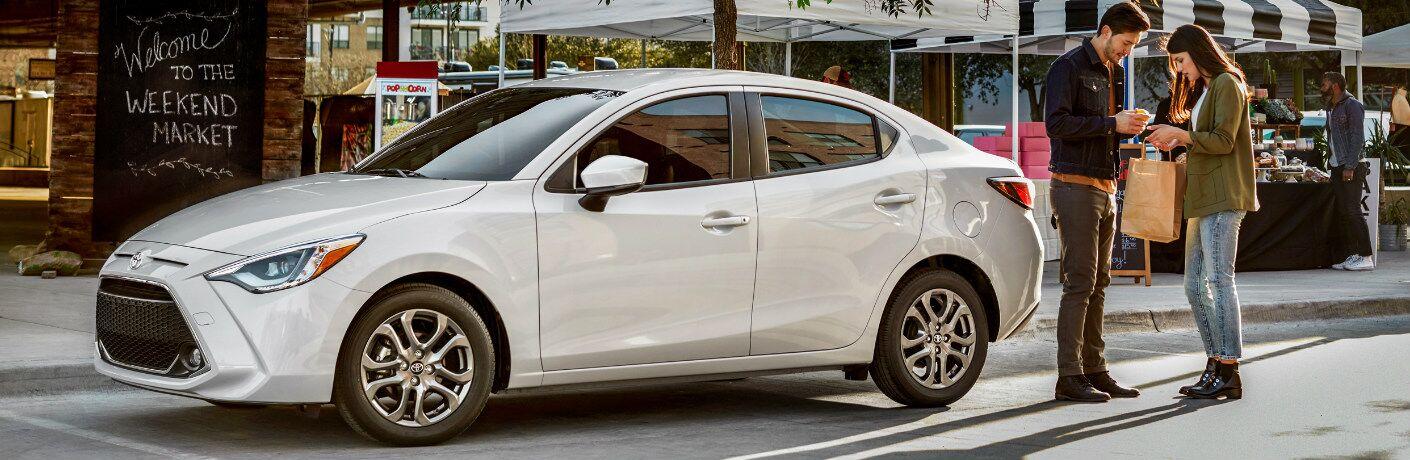 Man and Woman Standing next to a White 2019 Toyota Yaris Sedan
