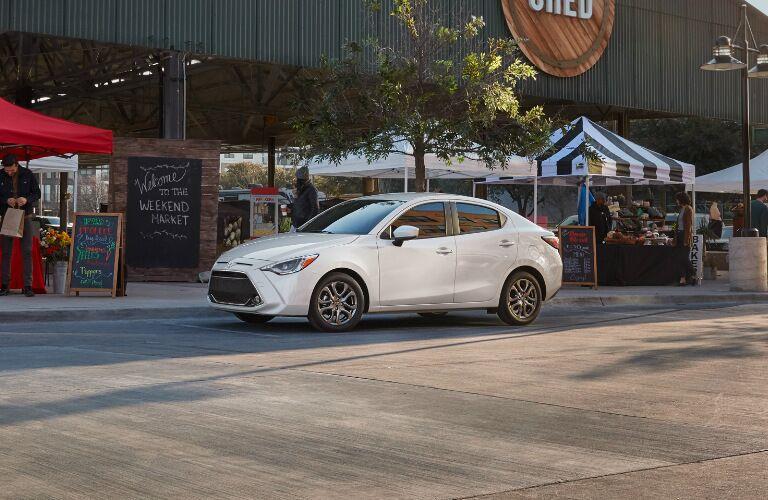 White 2019 Toyota Yaris Sedan Parked next to a Market