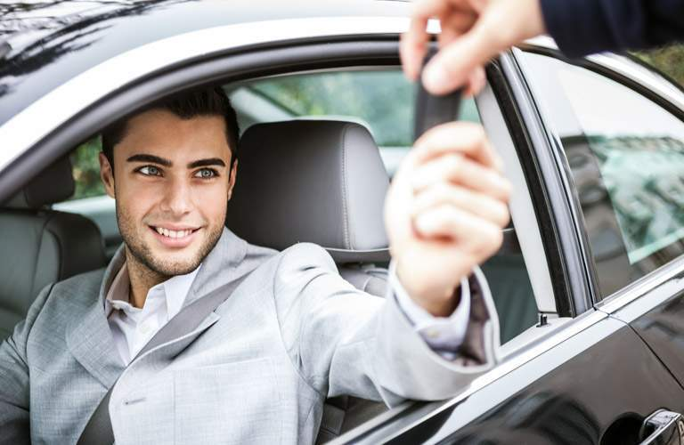 Person handing car key to man in driver's seat of car