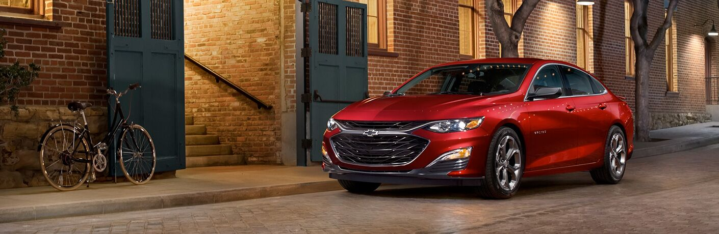 red 2019 Chevrolet Malibu parked in front of apartments