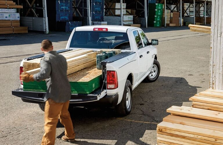 Man Loading Lumber Into Bed Of White Truck