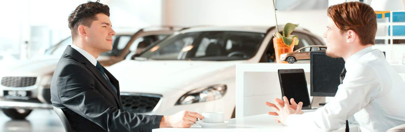 salesman and customer sitting across from each other in auto dealership