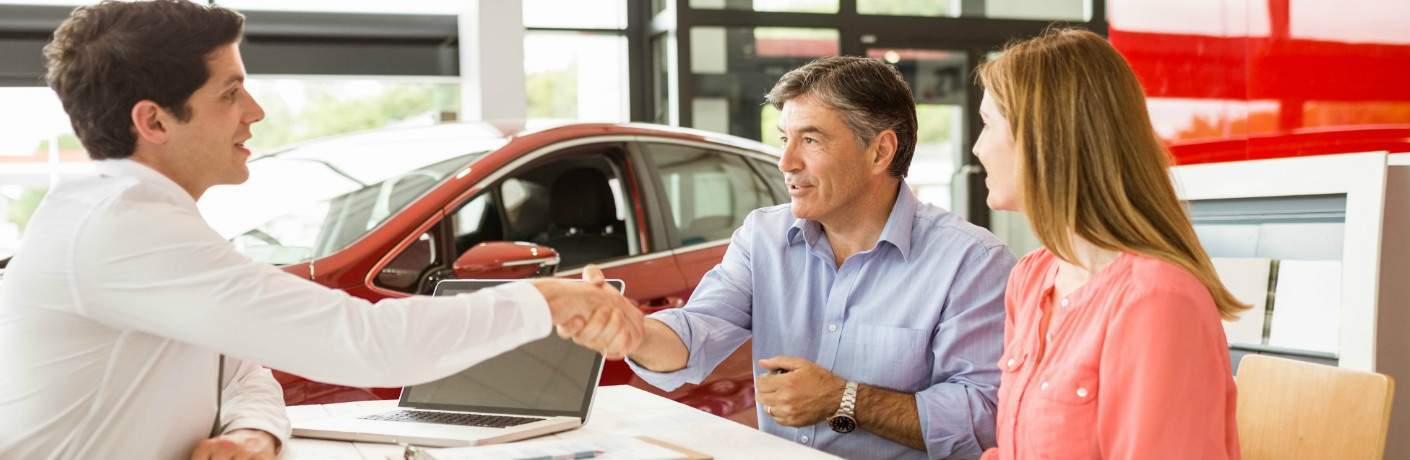 car salesman shaking hand of man and woman in dealership
