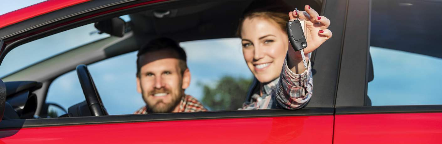 young couple in vehicle smiling and showing keys
