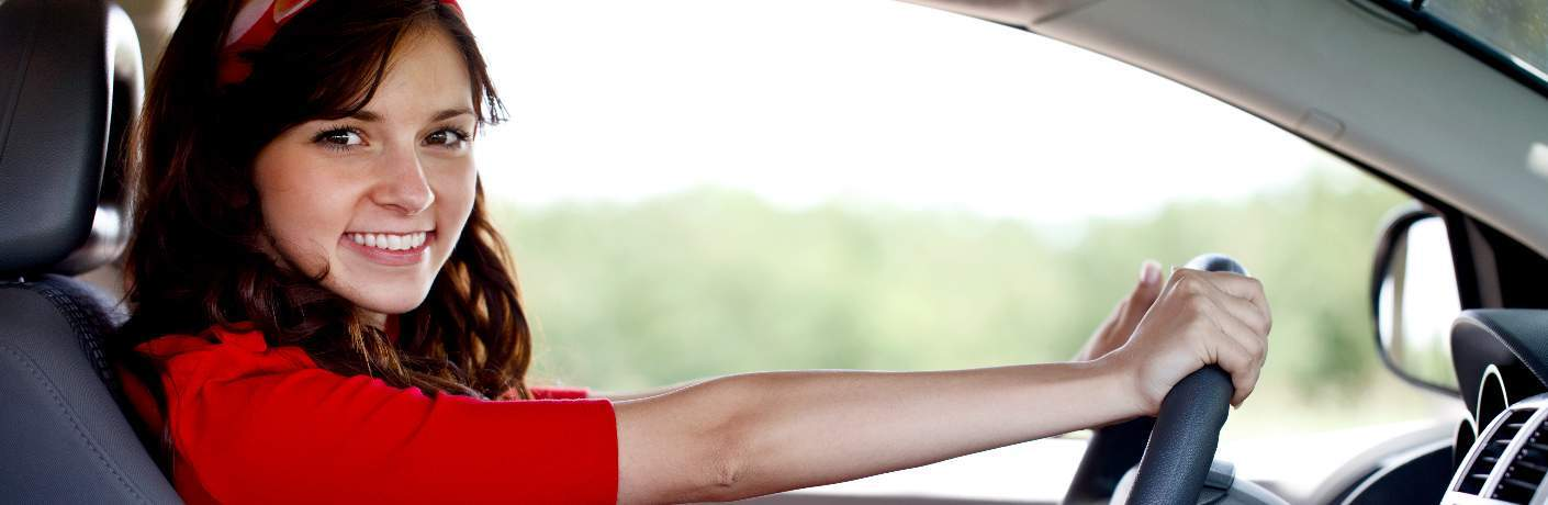 young woman behind wheel of car smiling at camera