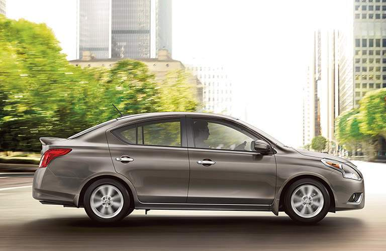 silver 2017 nissan versa driving on city street