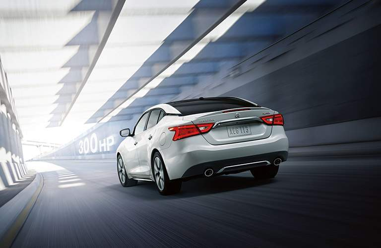rear of white 2018 nissan maxima driving through tunnel