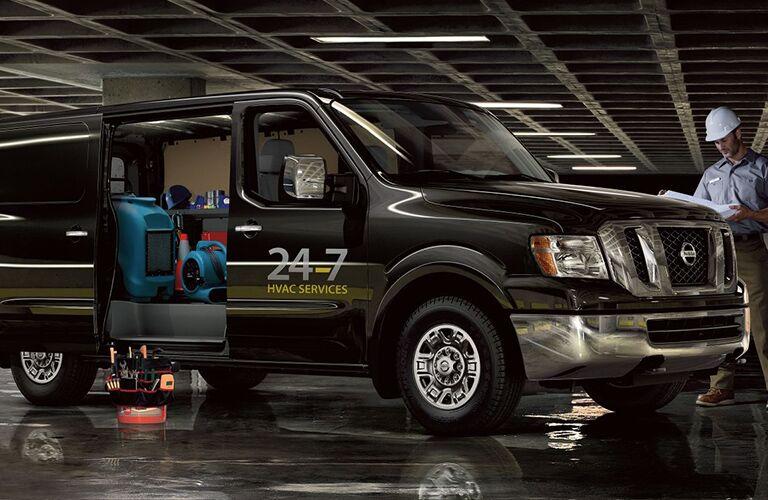 man in hard hat next to black 2018 nissan nv cargo van with doors open and supplies inside