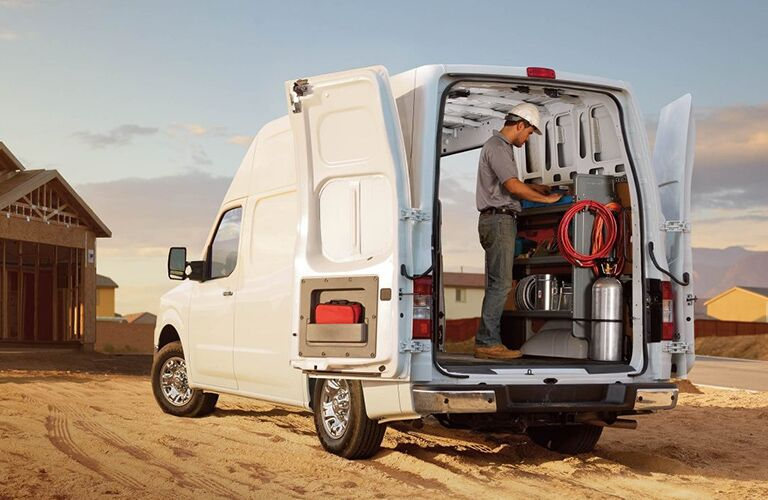 man in hard hat in rear of white 2018 nissan nv cargo van at construction site