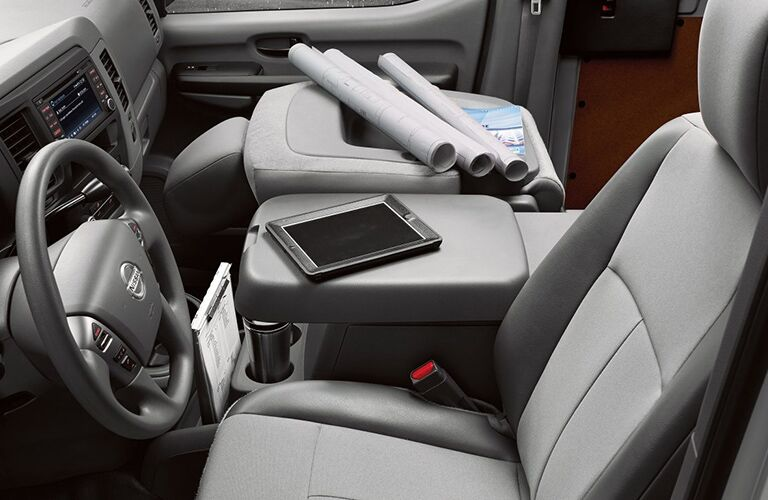 front interior of 2018 nissan nv cargo van with passenger seat folded down and electronics and papers on it