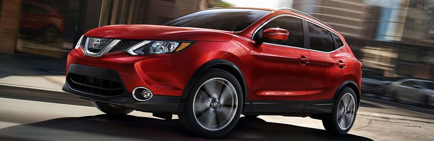 red 2018 nissan rogue sport driving in city
