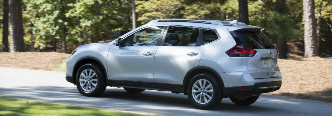 white 2018 nissan rogue driving through scenic road