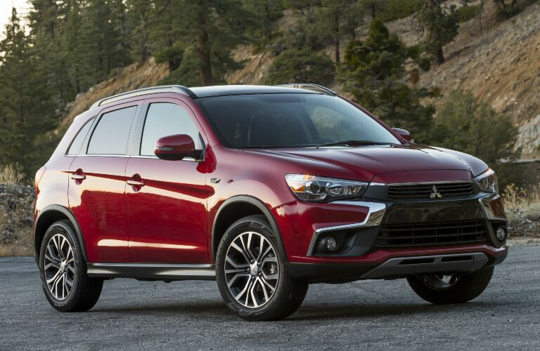 Red 2017 Mitsubishi Outlander Sport in front of a hill of pines