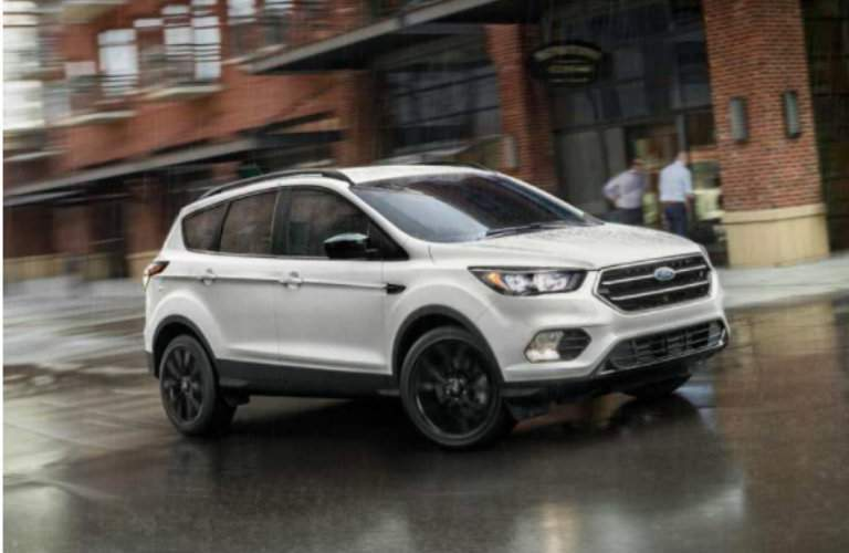 White Ford Escape driving on wet road