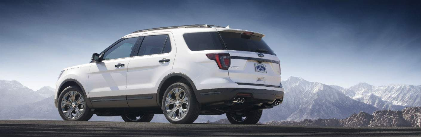 Rear profile shot of white 2018 Ford Explorer with mountains in background
