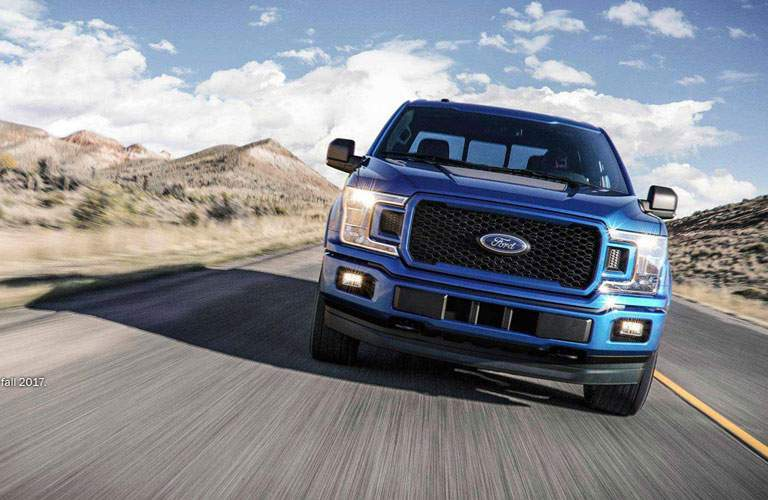 Blue 2018 Ford F-150 driving on empty highway road with desert landscape in background