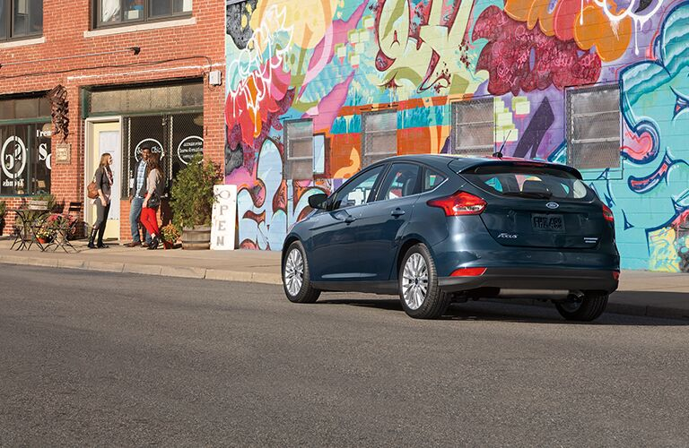 Rear view of 2018 Ford Focus parked in front of graffiti style wall