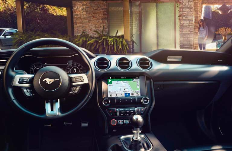 Steering wheel and dashboard inside 2018 Ford Mustang with gear shifter in frame