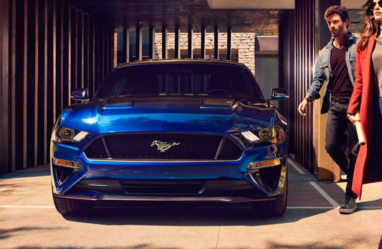 Front grille and headlights of blue 2018 Ford Mustang with two people walking towards it