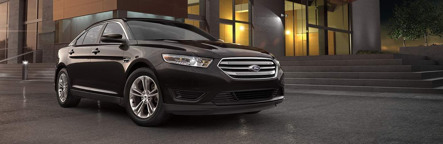 Black 2018 Ford Taurus parked in front of building at night