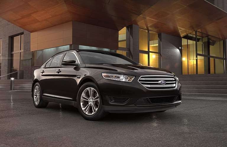 Wider shot of 2018 Ford Taurus parked in front of modern-styled building