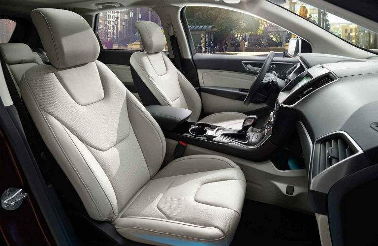 Front row of seating in 2018 Ford Edge with steering wheel and center console prominently shown