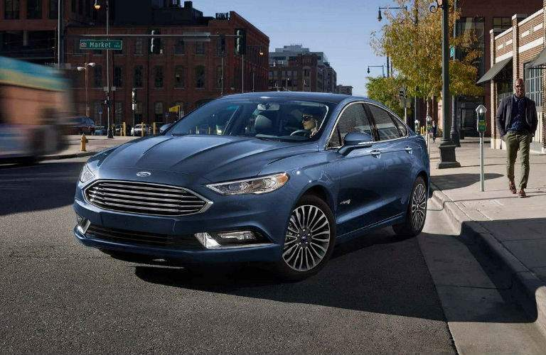 Woman pulling blue 2018 Ford Fusion out of parking space as man walks by