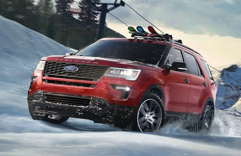 front view of red 2019 Ford Explorer driving up snowy hill