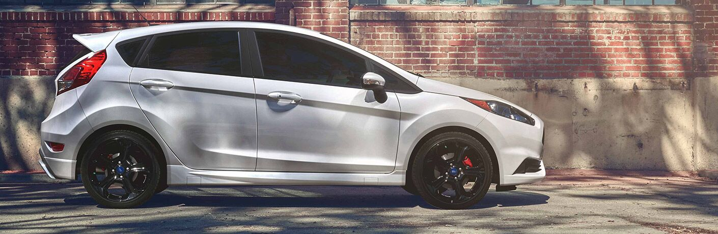 Profile view of white 2019 Ford Fiesta parked against brick wall