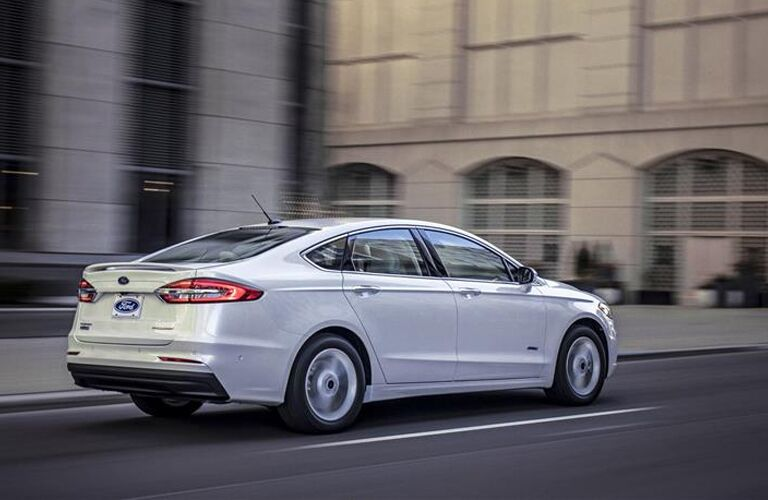 Rear view of white 2019 Ford Fusion driving in city